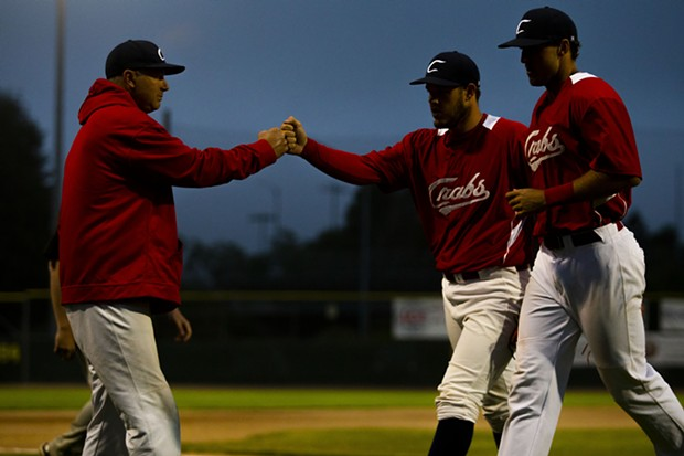 Crabs pitcher Wesley Harper (No. 32) fist-bumps with Crabs Manager Robin Guiver after completing an inning of work while heading back to the dugout on July 9, 2021. - THOMAS LAL