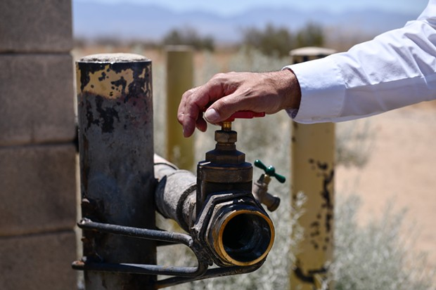 The vandalized water source where most water thefts occur in Lancaster, on July 2, 2021. The water is pumped into large containers that are sold and bought on the sides of the road. - PABLO UNZUETA FOR CALMATTERS