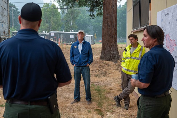 North Coast Congressmember Jared Huffman (center) listens as U.S. Forest Service command staff briefs him on the Monument Fire burning east of Willow Creek. - MARK MCKENNA