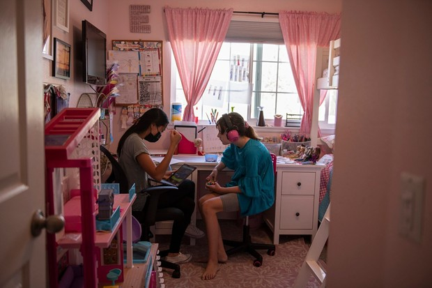 """Ellie sits in her room with a behavioral therapist during class time in Monrovia, on Sept. 15, 2021. """"There is no way to go back with 37 kids in a classroom,"""" Julie Fitzgibbons, the mother of triplets, said. """"With masks and not being able to communicate very well, and autism, there is just no way we can go back like normal."""" - PHOTO BY PABLO UNZUETA FOR CALMATTERS"""