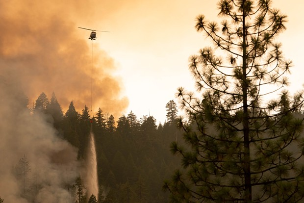 A helicopter drops water on the edge of the now 98-percent contained and lightning-caused McFarland Fire, which started July 29. - MARK MCKENNA