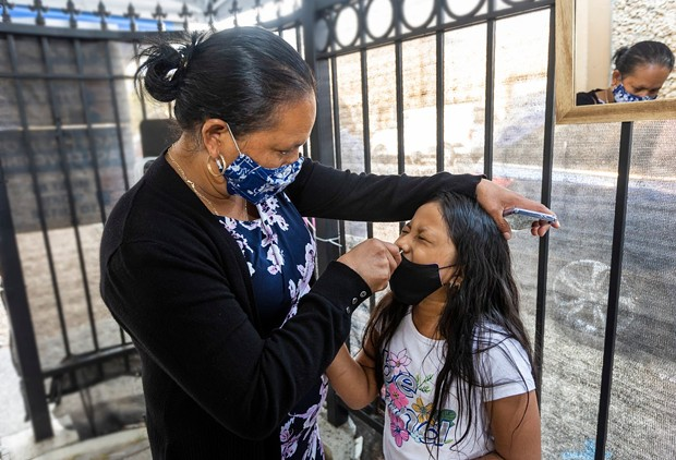 Maria Jimenez swabs her 7 year old daughter, Glendy Perez, for a COVID-19 test at Canal Alliance in San Rafael on Sept. 25, 2021. - PHOTO BY PENNI GLADSTONE FOR CALMATTERS