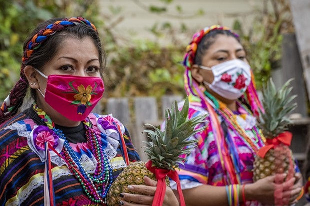 Dancers from Centro del Pueblo carrying pineapples used in their performance awaited the start of their dance in the garden at the Jardin Santuario. - PHOTO BY MARK LARSON