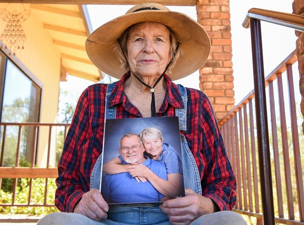 Johanna Trenerry of Happy Valley holds a photograph of herself with her husband, Art Trenerry, who died last year of COVID-19 while staying at Windsor Redding Care Center. His family members, including Johanna, are named as plaintiffs in a lawsuit against the facility. - PHOTO BY MATT BATES FOR CALMATTERS