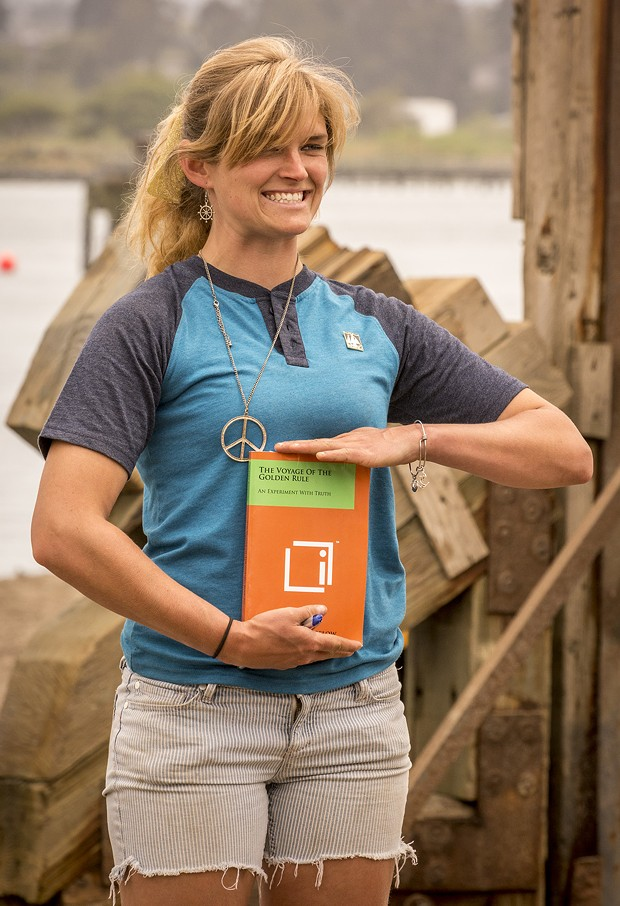 "Long-time volunteer and self-described ""jack-of-all trades"" Libby Tonning, of Manila, poses with one of the books about the Golden Rule prior to its launching at the Zerlang & Zerlang boat yard on the Samoa peninsula. - MARK LARSON"