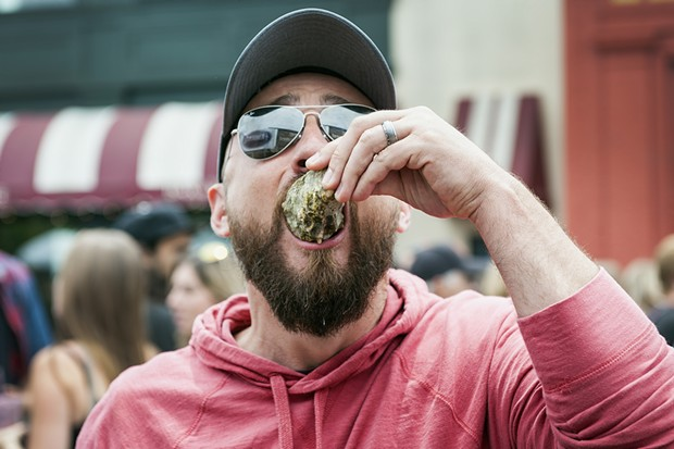 Adam Dietrich takes down an Oyster from the Humboldt Made booth at the 25th Annual Oyster Festival. - MARK MCKENNA