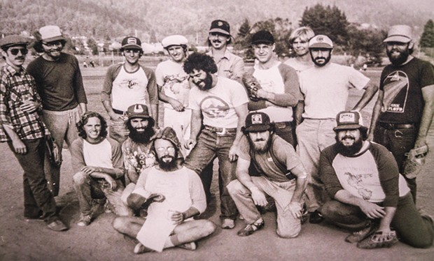 The NEC's softball team, the Snail Darters, in the late 1970s or early 1980s. Dominitz is seated in the front-left with a baseball mitt on his head. - CHRIS JENICAN BERESFORD