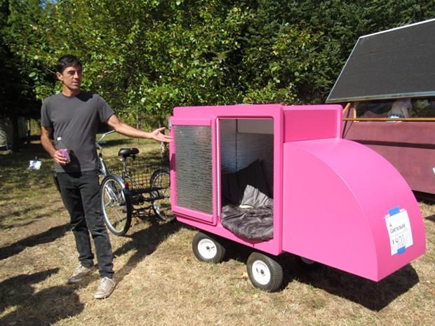 Carpenter Chris Housely demonstrates a tiny portable shelter he built, which is meant to be towed behind a bicycle. - LINDA STANSBERRY