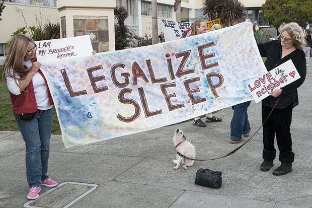 "Carla Ritter, left, and Carlene ""CC"" Schultz, both of Fieldbrook, hold a banner supporting the decriminalization of sleeping in public. Schultz says she spent a year houseless in Humboldt County before getting a home. She said she had also been a ""street mom"" for eight to 10 years helping kids on the street and others when she had an RV. - MARK MCKENNA"