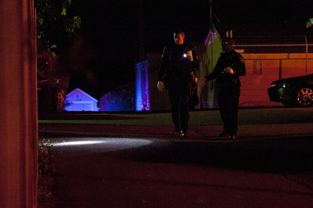 EPD officers search the scene of Saturday's shooting. - MARK MCKENNA