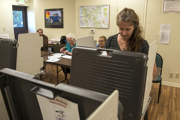 Kelly Erben casts her ballot at a local precinct, which turned out to be pretty lonely places on Election Day. - MARK MCKENNA