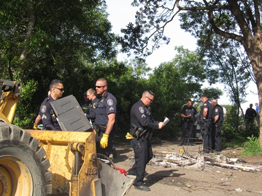 Officers clear out the first camp. - LINDA STANSBERRY