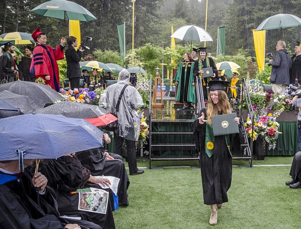 Journalism graduate Rebekah Staub displayed her diploma as she left the stage in a downpour at the College of Arts, Humanities and Social Sciences commencement on Saturday morning, May 14 in HSU's Redwood Bowl. - MARK LARSON