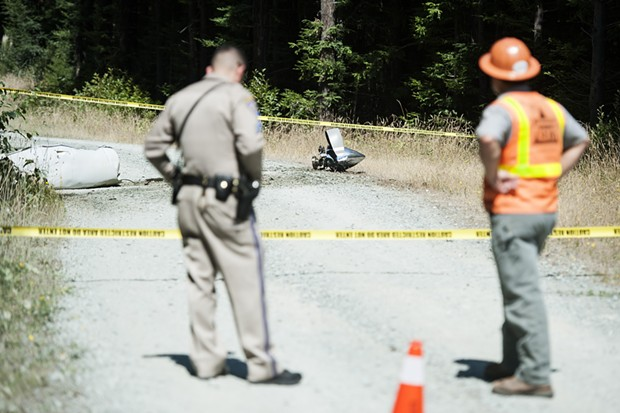 What appears to be part of a plane engine and propeller lie on an access road near the crash site. - MARK MCKENNA