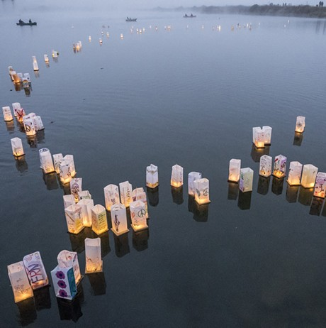 Personalized paper lanterns drift out onto Klopp Lake on Saturday night. - MARK LARSON