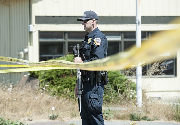 An officer guards the police line at the scene of a standoff in McKinleyville on Wednesday. - MARK MCKENNA