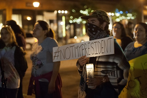 Ernesto Najera holds a sign at Thursday night's protest.