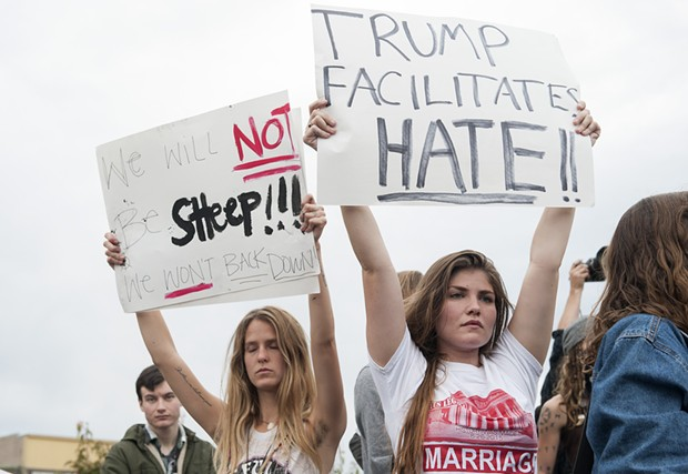 Julie Shonkwiler, a Humboldt State University senior and psychology major, left, and Brianna Jensen, also a senior and psych major at HSU, held signs during an anti-Trump demonstration at the Arcata Plaza on Friday. - MARK MCKENNA
