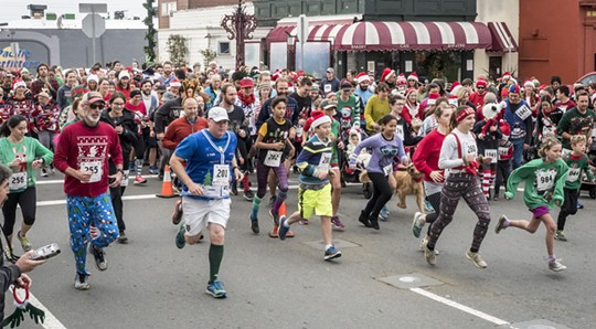 """The crowd of racers putting the """"sweat"""" in """"sweater"""" during Sunday's Ugly Sweater Run. - MARK LARSON"""