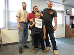 Three generations of growers, Rain on the Earth with her nephews Mark Switzer (far right) and grand-nephew Myles Moscato (center) pose with Wall as Moscato proudly holds the receipt for his application, the first submitted in the county. - LINDA STANSBERRY
