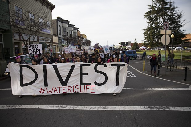 Led by seven indigenous youth, the group of protesters heads up G Street toward Wells Fargo, where several community members closed their accounts on Saturday. - SAM ARMANINO
