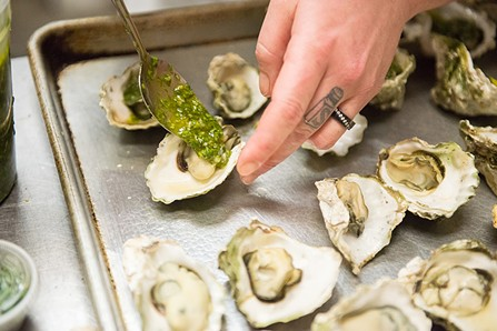 Lizette Acuna spoons an Argentinan Chimichurri on a grilled oyster. - MARK MCKENNA