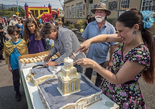Shoshanna Rose (right), of Arcata, helped cut and serve the Creamery Building replica cake that building owners Lisa and Brian Finigan, of Arcata, brought to share with Fervor Fest attendees. - PHOTO BY MARK LARSON