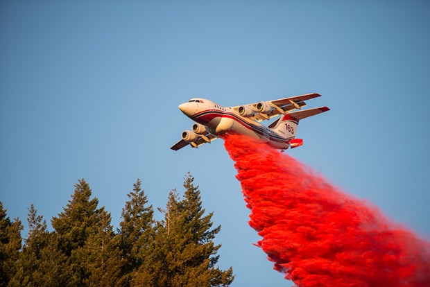 A plan drops a fire suppressant on a blaze yesterday near Blue Lake. - MARK MCKENNA