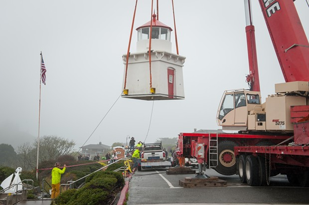Two workers use ropes to align the lighthouse as it is moved to a trailer. - MARK MCKENNA