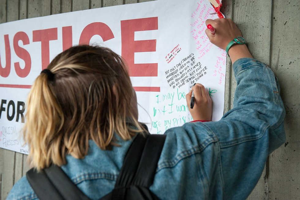 """A student signs the """"Justice for Josiah"""" banner. - PHOTO BY MARK MCKENNA"""