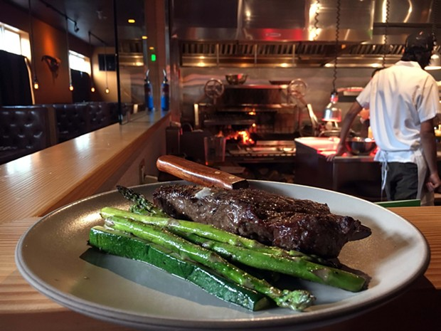 The New York strip steak, grilled vegetables and a counter view of the fire. - JENNIFER FUMIKO CAHILL
