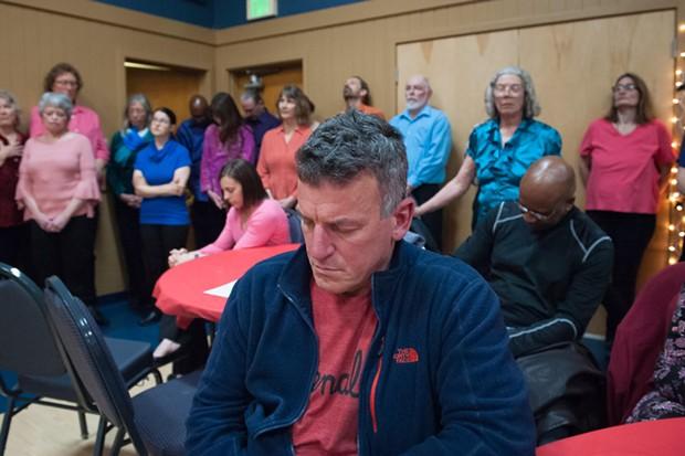 HSU campus police chief Donn Peterson closes his eyes during the prayer. - MARK MCKENNA