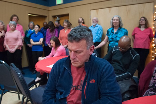 HSU campus police chief Donn Peterson closes his eyes during the prayer. - MARK MCKENNA