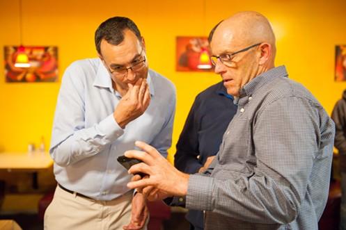 Incumbent Fifth District Supervisor Ryan Sundberg (left) eyes the narrow election results on Mike Pigg's phone. - MARK MCKENNA