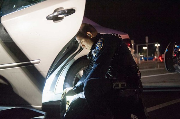 EPD officer Raymond Nunez searches a backpack in the WinCo parking lot. - PHOTO BY MARK MCKENNA