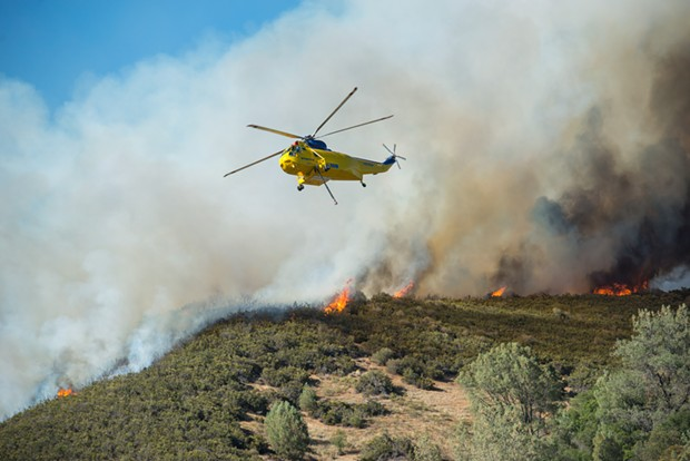 A Sikorsky helicopter prepares to refill its water hold to combat the Pawnee Fire earlier this week. - MARK MCKENNA