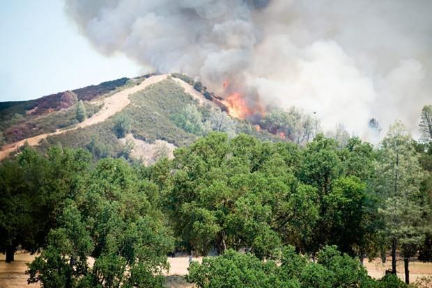 Fire breaks over a ridge at the Pawnee Fire last week. - MARK MCKENNA