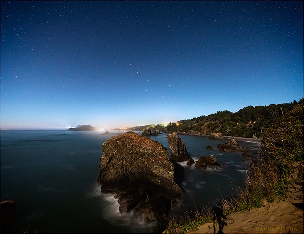 At the western edge of the North American continent, on the rough shores of the great Pacific Ocean, Trinidad, Humboldt County, California, sparkles in the moonlight under a starry sky. The Big Dipper and Polaris, the North Star, have been enhanced for recognizability.