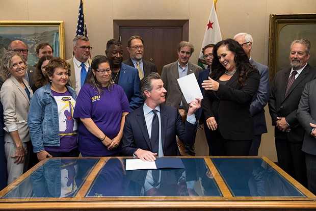 Gov. Gavin Newsom after signing the controversial Assembly Bill 5, with the legislation's author Assemblymember Lorena Gonzalez (right).