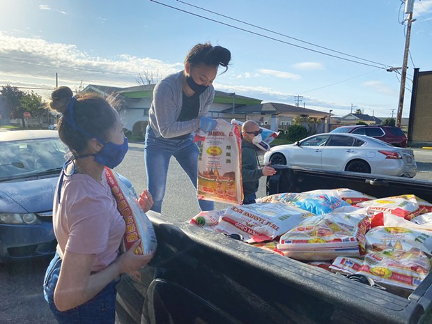 Bao Syphanthong, Pang Lo and Yuhmong Lo load a truck with rice sacks to be distributed to Hmong and Lao families in need.