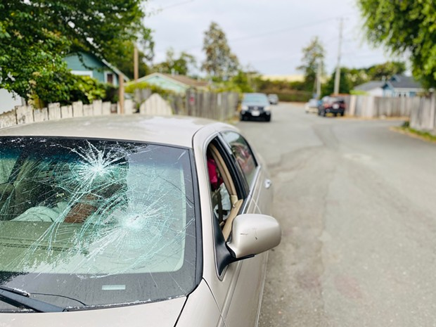 An old car sits with its windshield busted on Howard Street.