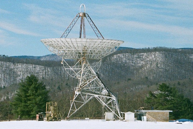 """The 85-foot Green Bank WV radio telescope used by Frank Drake in 1960 to monitor two relatively nearby stars for signs of life by """"listening"""" to the wavelength emitted naturally by interstellar hydrogen."""