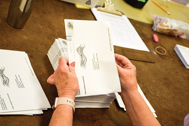 A volunteer prepares vote-by-mail ballots for counting in 2018.