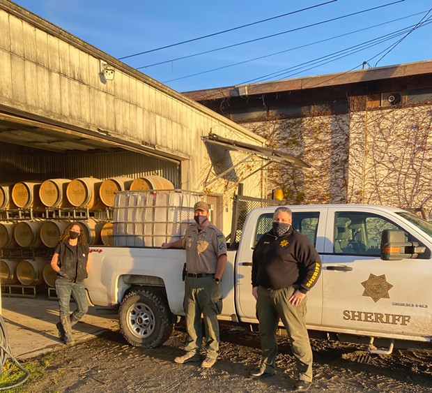 Alchemy Distillery's Amy Bohner with Ryan Craig and Jason Benge picking up a load of grain for the SWAP farm.