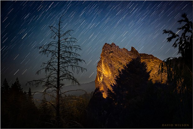 A great rock outcrop rests in a remote river valley beneath the stars on California's North Coast. Moonlight illuminated the landscape beyond, while some light from nearby human activity temporarily shone upon the rock itself in this 346-second exposure. July 13, 2021.