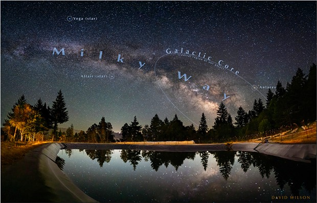 Ringed by trees, a giant catchment pond reflects the magnificent sky at Schackow Farm in Humboldt County. A crescent moon sinking in the west illuminates the far hills across the Eel River Valley. The galactic core will sink beneath the horizon a little each night through the fall until it is no longer visible in our night sky, to return after the spring. June, 2021.