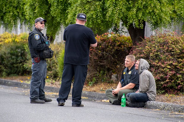 Undersheriff Justin Braud sits with wanted fugitive Matthew Dilley moments after Dilley surrendered his pistol, concluding an hours-long standoff with police in McKinleyville.