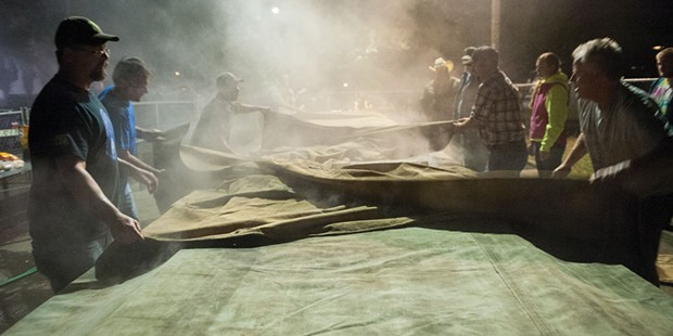 Tarps are spread over the smoking covered barbecue pits at the Fortuna Rodeo.