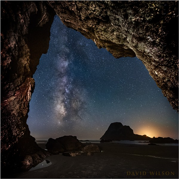 The Milky Way rises from the horizon near the glow of the setting crescent moon outside of this hidden Houda Beach cave. Camel Rock's silhouette is large on the horizon beside the glow of the setting crescent moon. Humboldt County, California. September 13, 2018. - DAVID WILSON