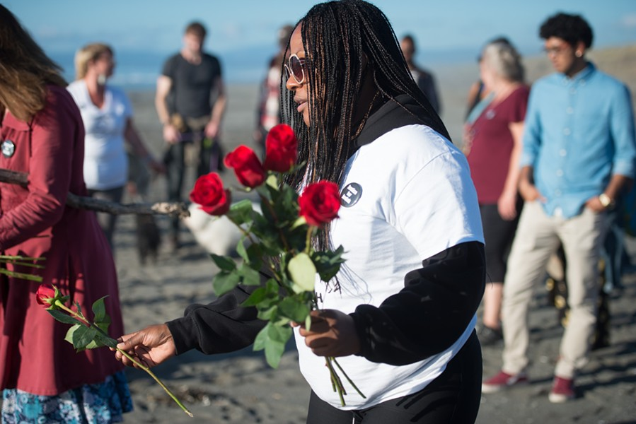 Charmaine Lawson places roses in two hearts drawn in the sand at a recent vigil held for her son. - MARK MCKENNA